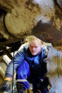 Avtapping av olje. Traktoren blir køyrt godt varm først, slik at olja renn lett ut og tek med seg alt av smuss og partiklar ut av motoren.