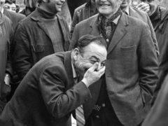 """Folkemengda, som det osar humør av, er fotografert i mars/april 1972. Det var auksjon på Vangen (Aurlandsvangen). Eg meinar å hugsa at auksjonarius var Odd Nesse, lensmann i Leikanger. Han var munnrapp og vittig, noko tilhøyrarene sette pris på. Fotografiet er eit """"hofteskot"""", eg torde ikkje løfta kamera til auga. Smilande kar med hatt er Nils Skahjem. Han som ler seg krokete, fremst i biletet, skal vera Ingebrigt Fimreite."""